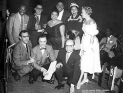 From left to right: standing: Buddy Johnson, Norman Orleck (Cashbox), Ella Johnson, Joe Turner, Lou-Willie Turner, Jackie Frego; kneeling: Jerry Wexler, Alan Freed, Ahmet Ertegun